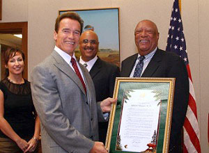 California Governor Arnold Schwarzenegger admires the Senate Resolution presented to Sylester Flowers on September 5, 2007, while son Eric Flowers and his wife look on.